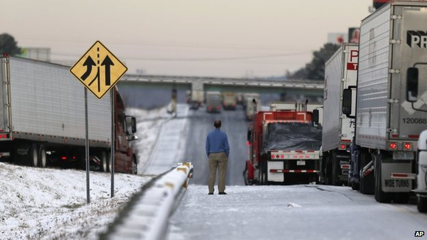 A man stood on a frozen roadway along Interstate 75 in Macon, Georgia, on 29 January 2014