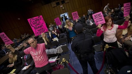 A Capitol Police officer monitors members of Code Pink as they hold up signs on Capitol Hill in Washington 29 January 2014