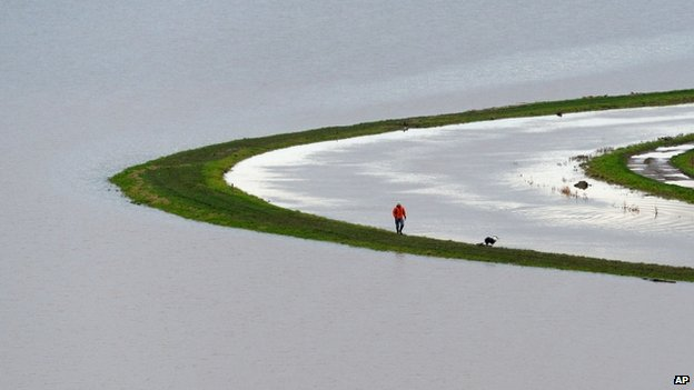 A man walks a dog between a river and a flooded field