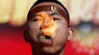A man holds burning dry grass in his mouth while spitting a flame during the opening of the temple fair for the Chinese new year celebrations at Ditan Park, also known as the Temple of Earth, in Beijing