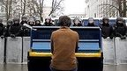 Man playing piano in front of line of riot police
