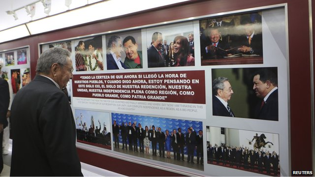 Cuban President Raul Castro looks on at an exhibit dedicated to the late Venezuelan leader Hugo Chavez