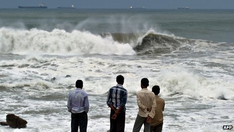 Men watch waves crash on beach in India