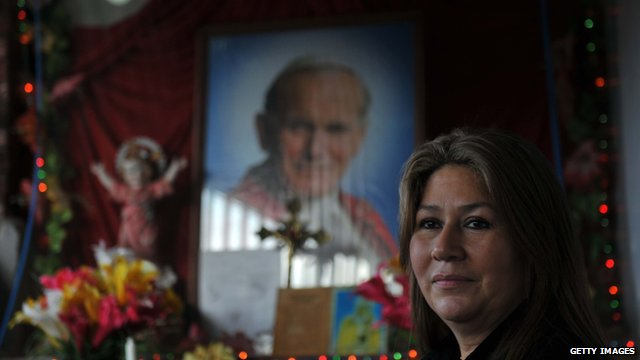 Floribeth Mora in front of a picture of John Paul II