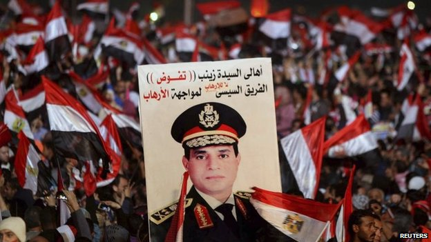 Supporters of the Egyptian military hold up a poster of Abdul Fattah al-Sisi in Cairo's Tahrir Square (25 January 2014)