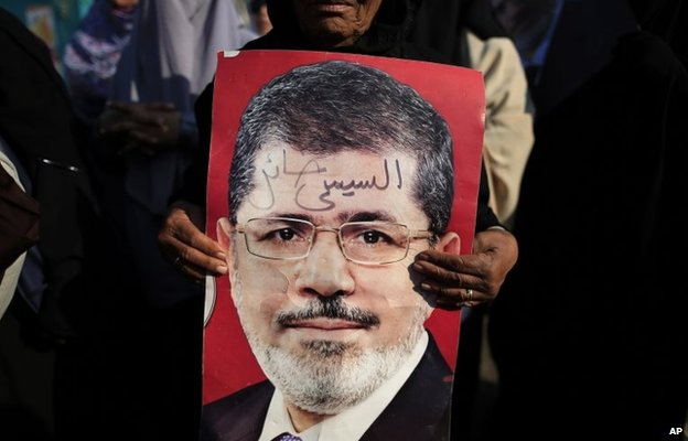 "A supporter of Mohammed Morsi holds up a poster saying: ""Sisi traitor"" at a protest in Nasr City, Cairo (4 July 2013)"