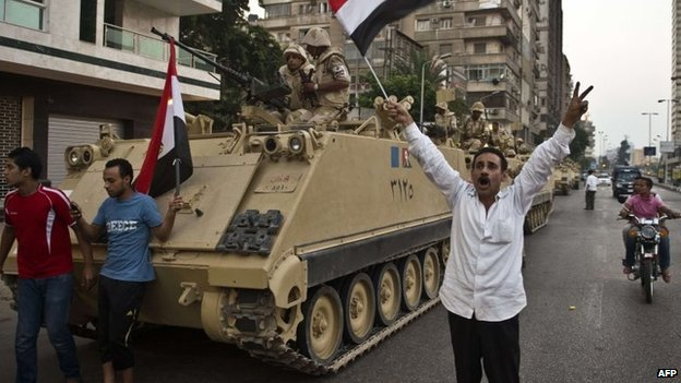 A man waves an Egyptian flag next to an armoured personnel carrier in Cairo (3 July 2013)