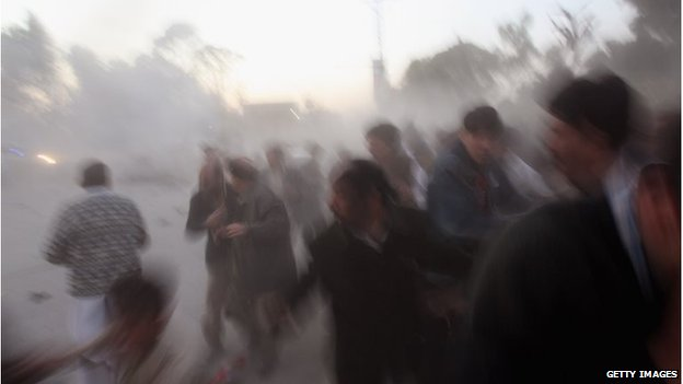 Survivors flee the bomb blast that killed Prime Minister Benazir Bhutto and around 15 others, on 27 December 2007
