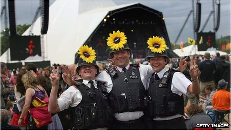 Three policemen at Glastonbury Festival with sunflowers in their helmets