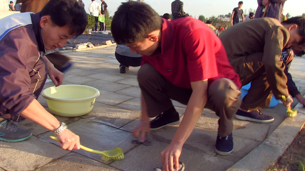 students clean North Korean monument