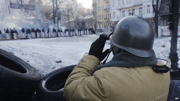 A protester looks through binoculars at riot police as he guards the barricades in Kiev, Ukraine, Thursday, Jan. 30, 2014