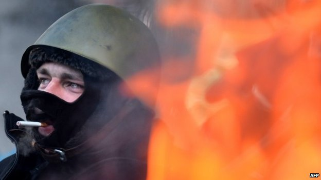 An opposition protester smokes a cigarette as he warms himself near a fire in the centre of Kiev on January 30, 2014