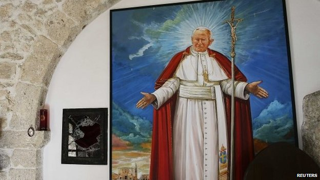 A broken glass of a niche where the reliquary with the blood of the late Pope John Paul II was located is seen next to a painting of the late Pope in the small mountain church of San Pietro della Ienca,