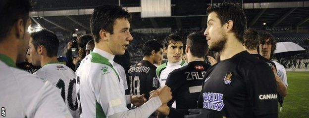 Racing Santander defender Saul Garcia  speaks with Real Sociedad defender Inigo Martinez