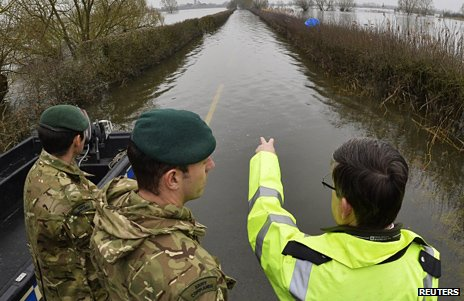 British army Royal Engineers are shown flooded areas by a Somerset emergency planning officer