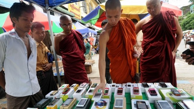 Buddhist monks look at mobile phones