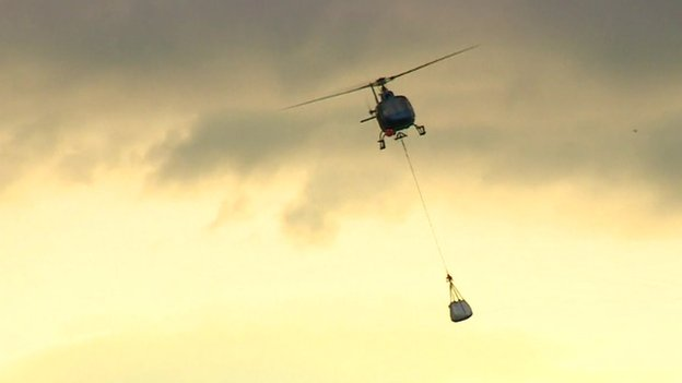 A helicopter carrying a large bag of slate suspended beneath it by a rope