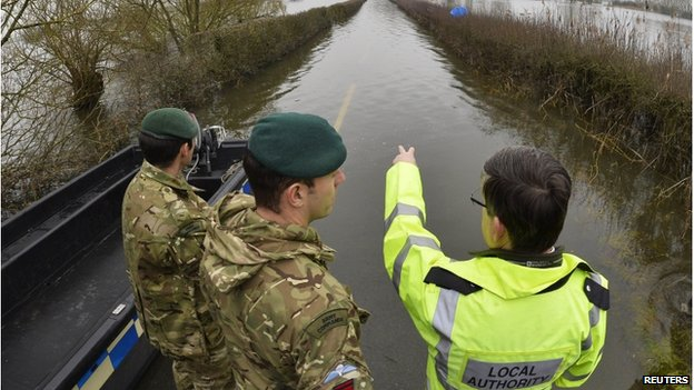 Two soldiers and a council worker look at a flooded road