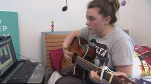 Rachel records her guitar playing using a webcam