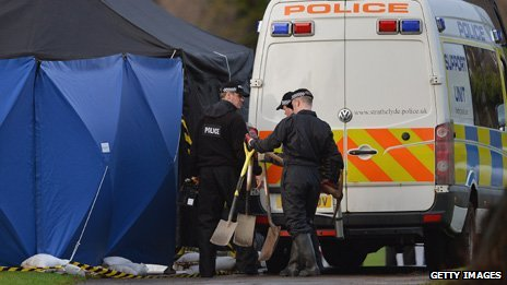 Forensic officers at the grave