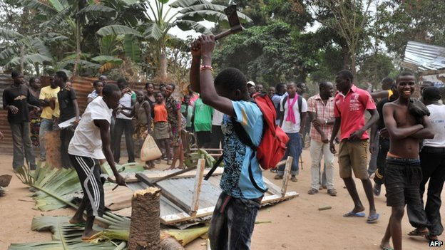 A looter cuts down a tree at a mosque in Bangui on 28 January  2014 after the departure of Seleka militants from the Kassai military camp in Bangui, CAR