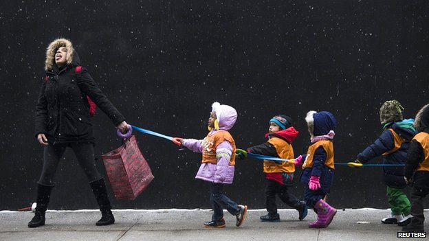 Teacher and pupils catching snowflakes in Harlem