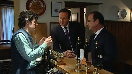 David Cameron and Francois Hollande talk to the landlord at the Swan Inn