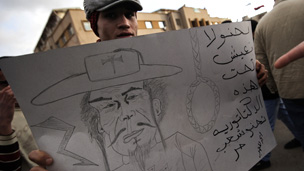 Protestor in Benghazi with Gadaffi cartoon