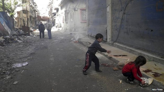 Children cut wood pieces in the besieged area of Homs January 28