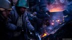 Anti-government protesters warm themselves at a fire near a barricade early morning in Kiev