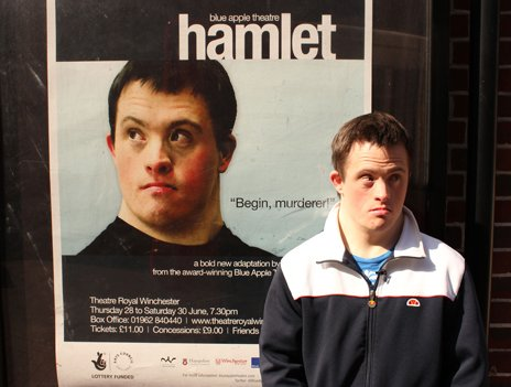 Tommy Jessop stands next to a poster of the play