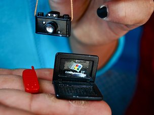 Woman holds miniatures of camera, laptop and mobile phone
