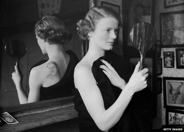 14th November 1936: A film fan uses a mirror to admire the image of film star Gary Gooper she has had tattooed on her back by George Burchett a London tattooist (C) Getty Images
