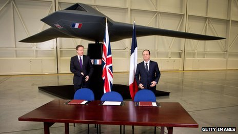 British Prime Minister David Cameron (L) and French President Francois Hollande stand beneath a model of an unmanned aircraft before holding a press conference during a one-day summit at RAF Brize Norton