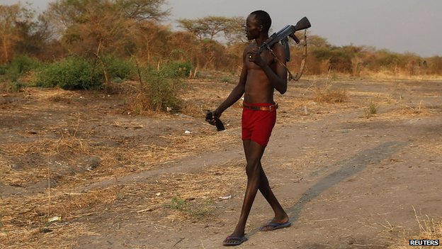 A rebel fighter with a weapon walks to a river to wash as he returns from a frontline in a rebel-controlled territory in Jonglei State, South Sudan (January 30, 2014)