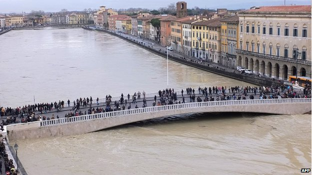 People stand on a bridge over the Arno river whose level rose following heavy rain over Pisa, on 31 January, 2014