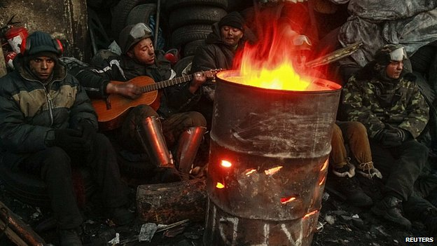 Protesters rest around a fire in Kiev