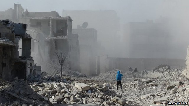 Man stands amid rubble in Aleppo