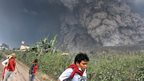 Villagers and a journalist prepare to flee as Mount Sinabung releases pyroclastic flows during an eruption in Namantaran, North Sumatra, Indonesia, Saturday, Feb. 1