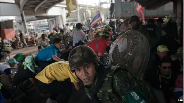 A Thai army soldier (front) and anti-government protesters takes cover as explosions and gun shots are fired during clashes with Thai pro-election protesters (not seen) in Bangkok on February 1