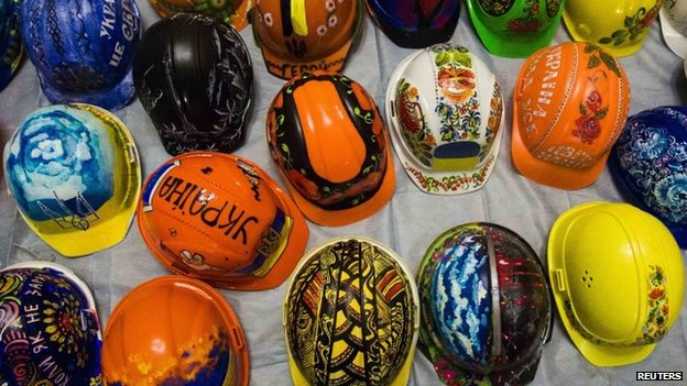 A collection of hardhats painted with motifs for anti-government protesters