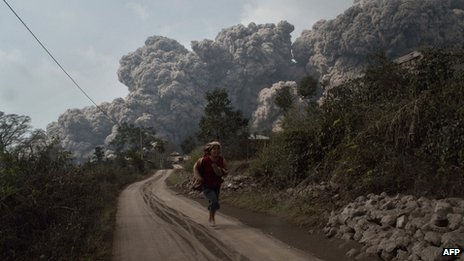 Person fleeing from erupting volcano in Sumatra