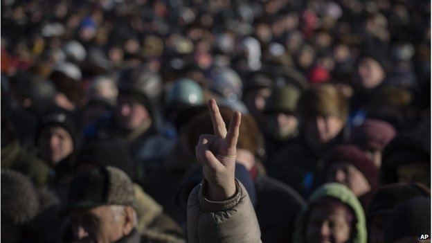 A person flashes a victory sign during a rally in Kiev, February 2