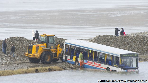 Council workers cleared the road near the stranded bus on Sunday