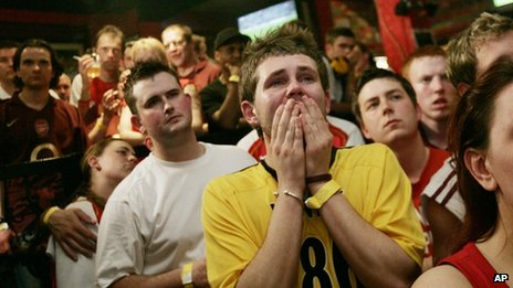 Upset fans watching Arsenal lose in a pub