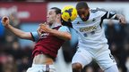 Swansea captain Ashley Williams challenges West Ham's Andy Carroll during their Premier League match at Upton Park