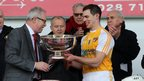 Ulster Council president Martin McAviney presents Antrim hurling captain Neil McManus with the Liam Harvey Cup