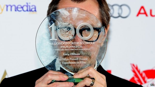 Gary Oldman hiding face with award