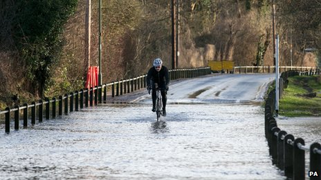 A cyclist rides drives through a flooded road next to the River Thames in Chertsey, Surrey