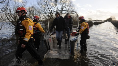 People disembark a fire and rescue boat used to ferry residents backwards and forwards to the flood-stricken Somerset village of Muchelney